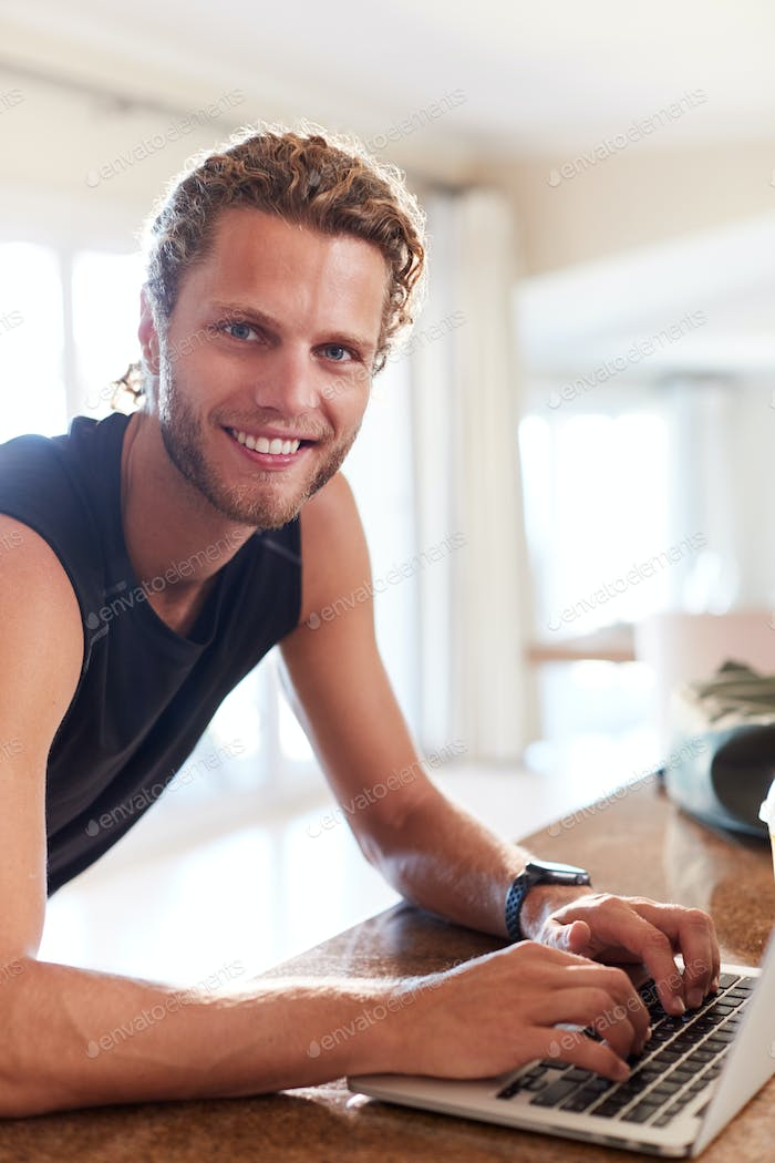 Millennial white man checking fitness app on laptop after a workout smiling to camera, vertical