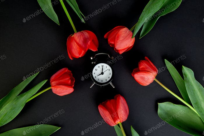 Black alarm clock near bouquet red tulips