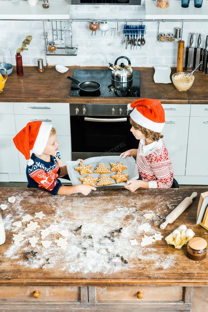 high angle view of adorable children in santa hats holding baking tray with ginger cookies