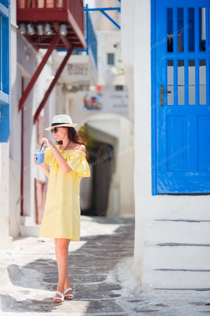 Young woman walking in narrow streets of old greek village in Greece