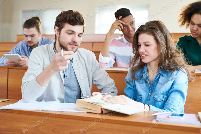 Cheerful students discussing textbook at break before seminar