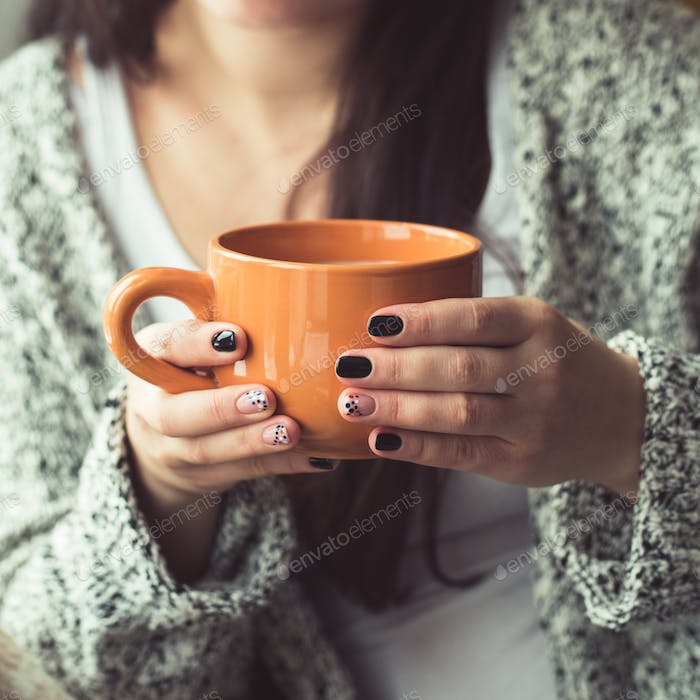 Woman with beautiful manicure holding a orange cup of cocoa