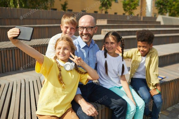 Kinder nehmen Selfie mit Lehrer im Freien