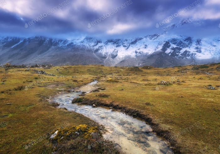 Mountains with snow covered peaks, small river, yellow grass