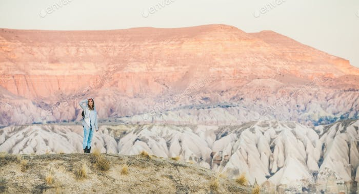 Young woman hiking in mountains among natural rocks of Cappadocia
