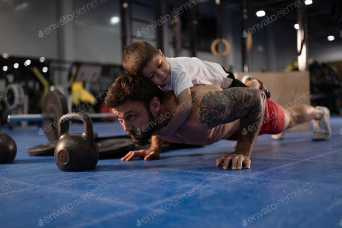 Father and son doing push ups together in gym