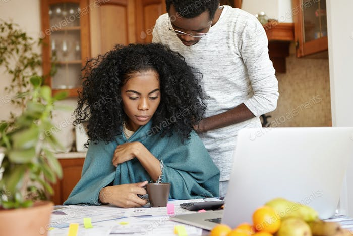 People, finances and paperwork. Candid shot of young African-American couple working through finance