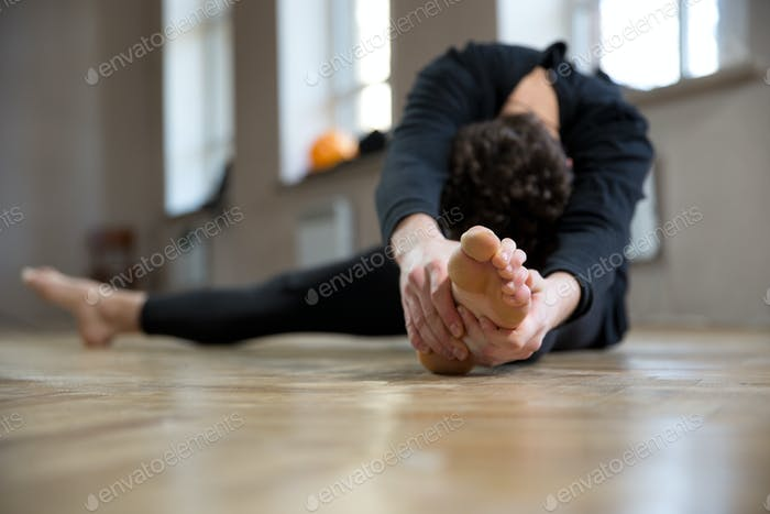 Man doing stretching exercise at gym