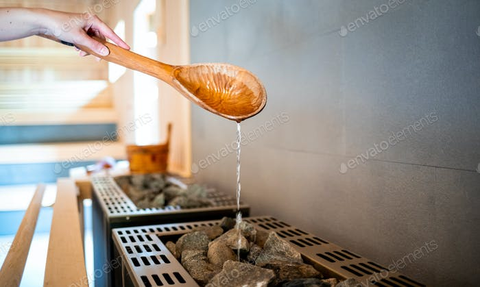 Pouring water on hot stone into heater in sauna
