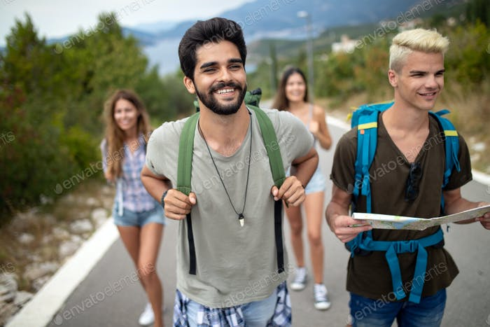 Group of young people with backpacks walking together by the road