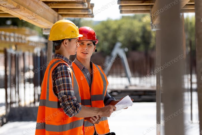 Two civil engineers dressed in orange work vests and helmets discuss the construction process on the