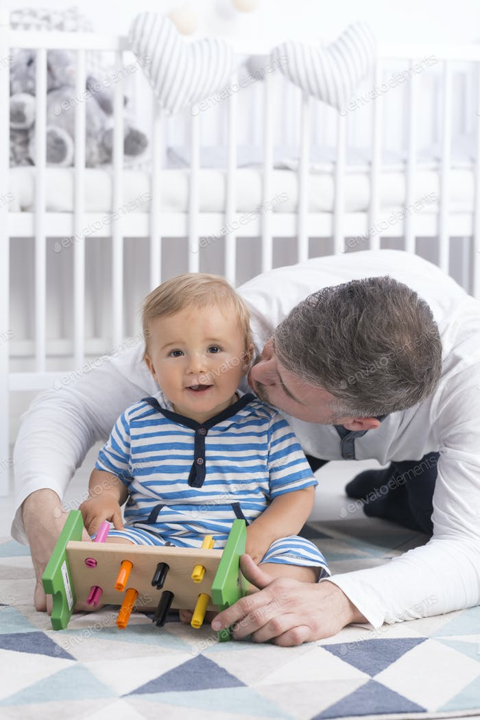 Dad kissing small smiling baby