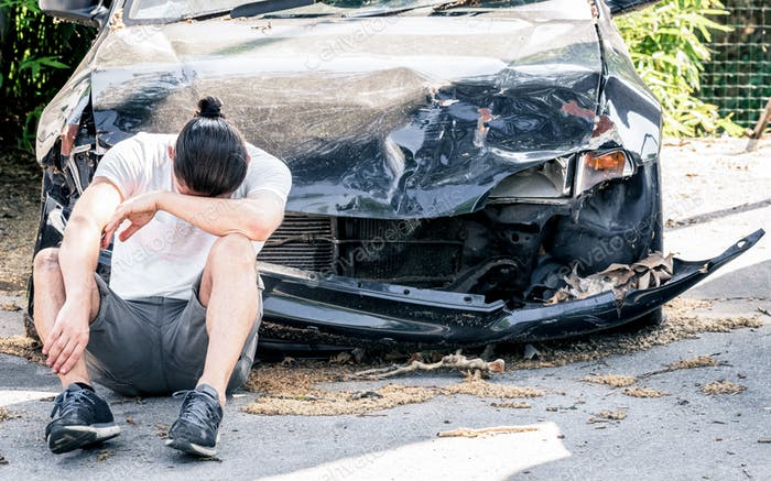 Hombre llorando en su viejo coche dañado después de un accidente