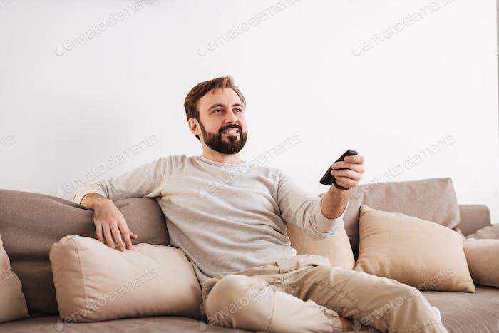 Porträt eines lächelnden Mannes mit Fernbedienung