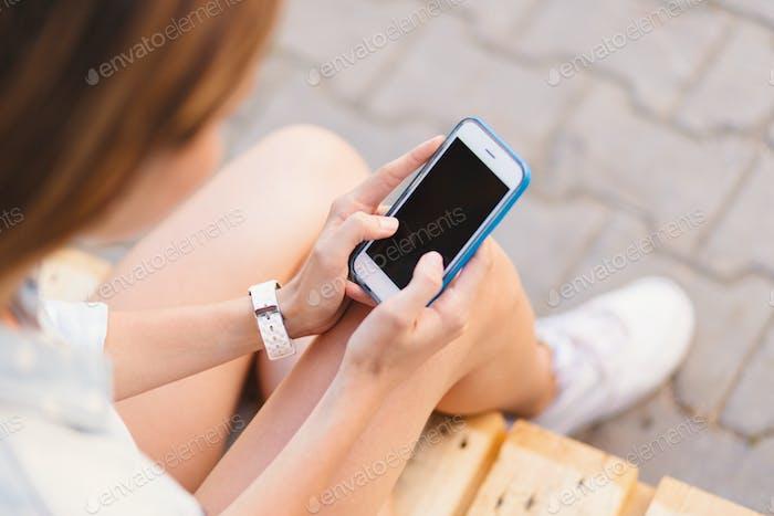 Mujer bonita sosteniendo el teléfono en las manos mientras toca la Completa