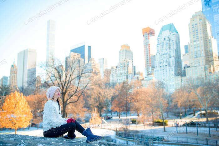 Beautiful woman enjoy the view of ice-rink in Central Park and skyscrapers on Manhattan in New York