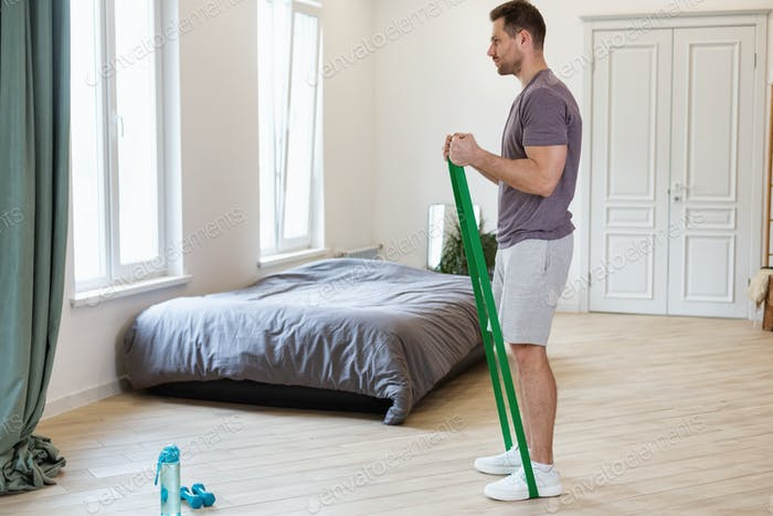 Man Exercising Using Resistance Bands Loop Training At Home