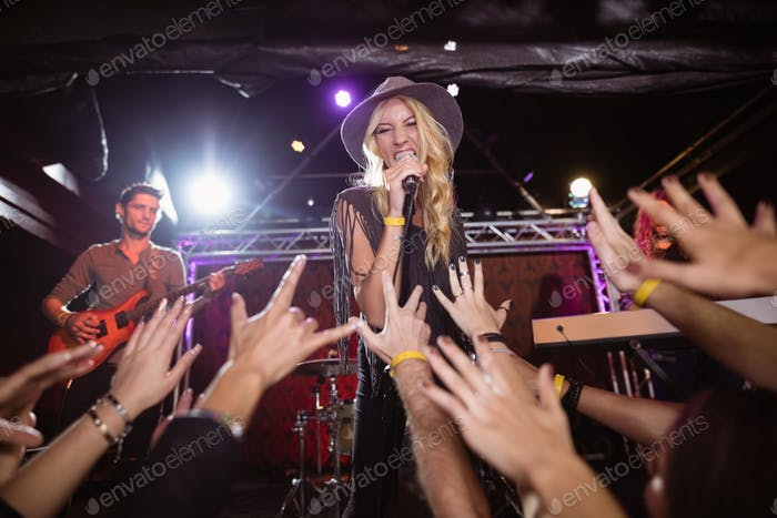 Cheerful female singer performing on stage at nightclub