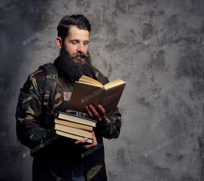 Handsome bearded hipster, dressed in a trendy camouflage jacket in a studio