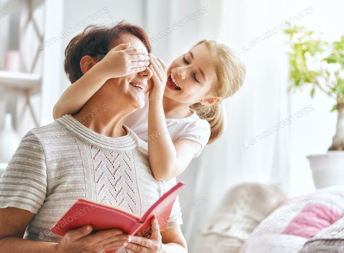 Grandmother reading a book to granddaughter