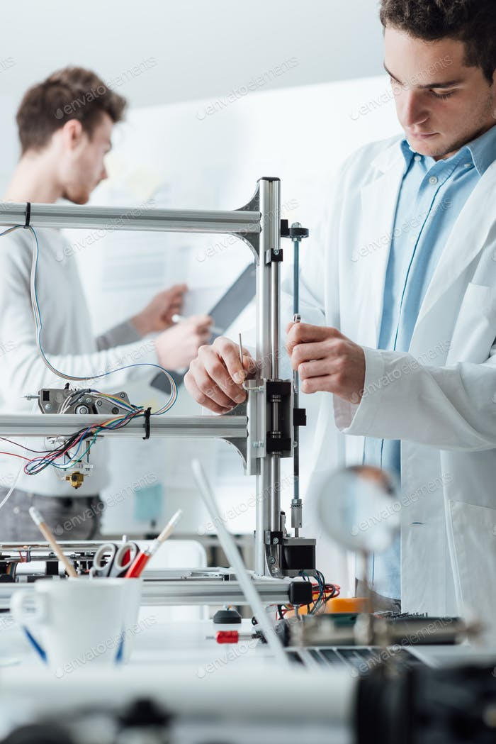 Engineers in the lab using a 3D printer