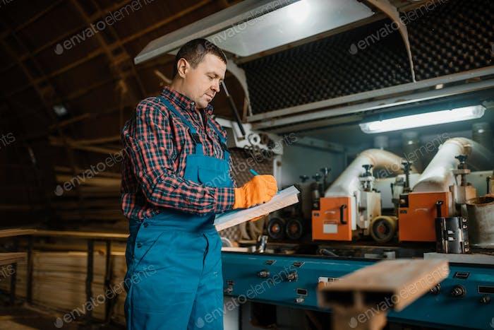 Плотник в форме держит ноутбук, пиломатериалы