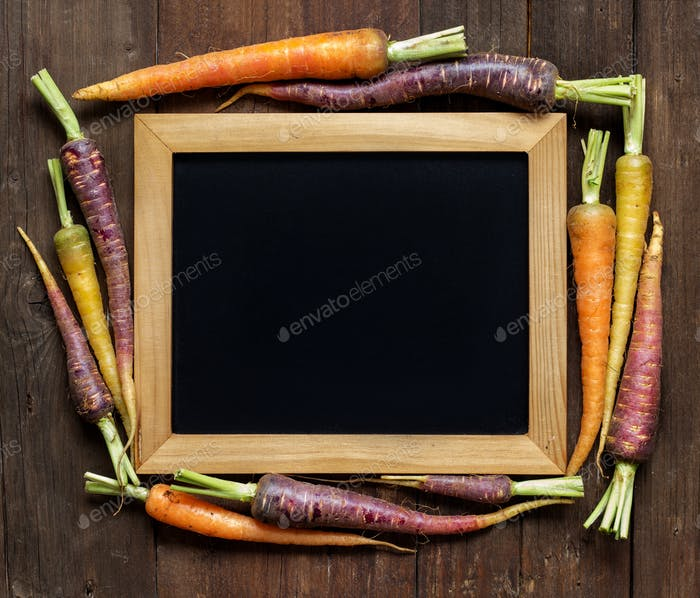 Fresh organic rainbow carrots and chalkboard on wood