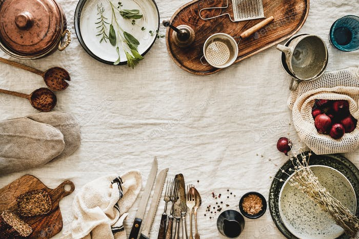 Various kitchen utensils and tablewear over linen tablecloth, copy space