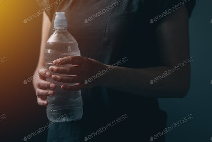 Woman with bottle of fresh drinking water