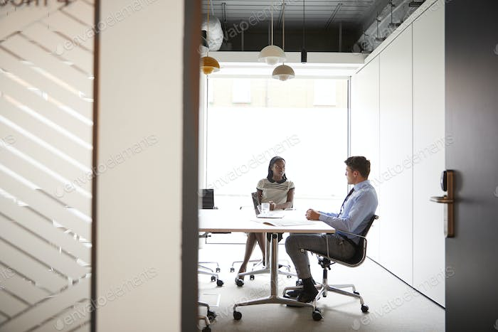 Businessman And Businesswoman Having Discussion Around Boardroom