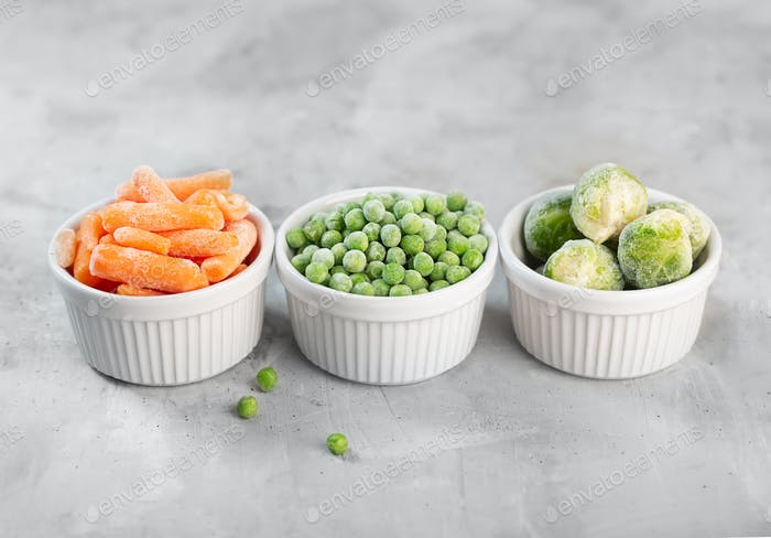 Frozen vegetables such as green peas, brussels sprouts and baby carrot in the white bowls