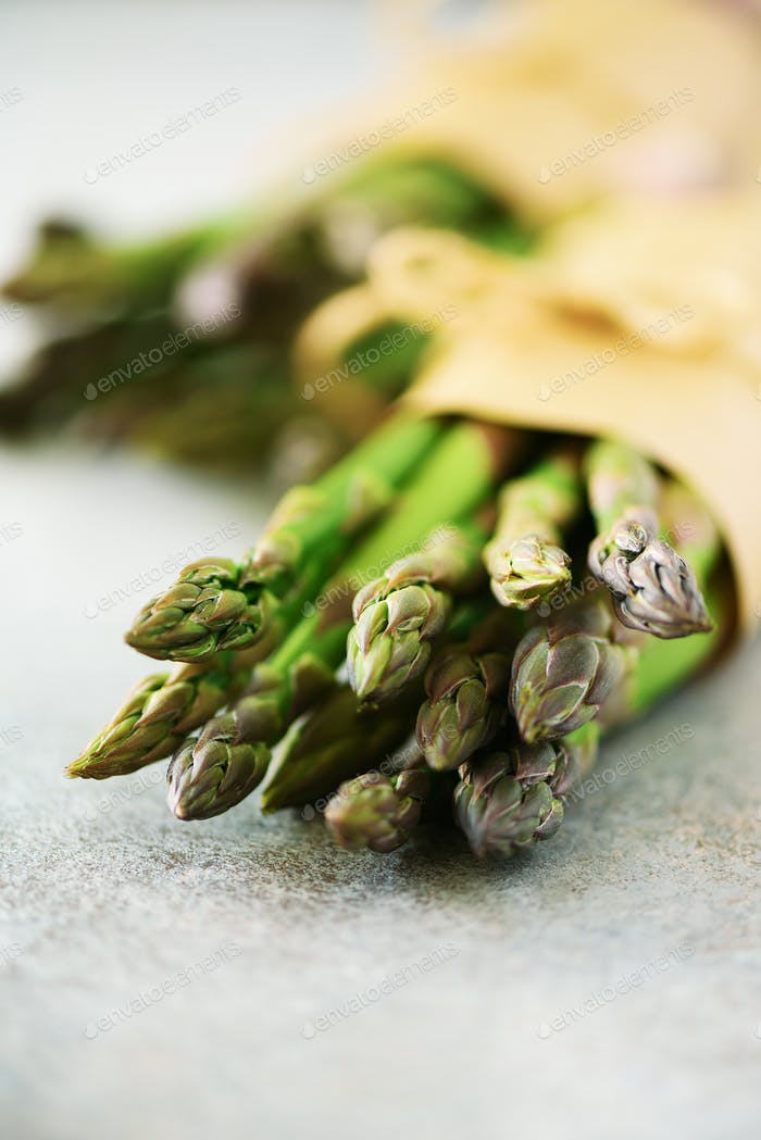 Bunch of fresh asparagus on gray backgrouns. Asparagus on craft paper with packthread. Raw, vegan