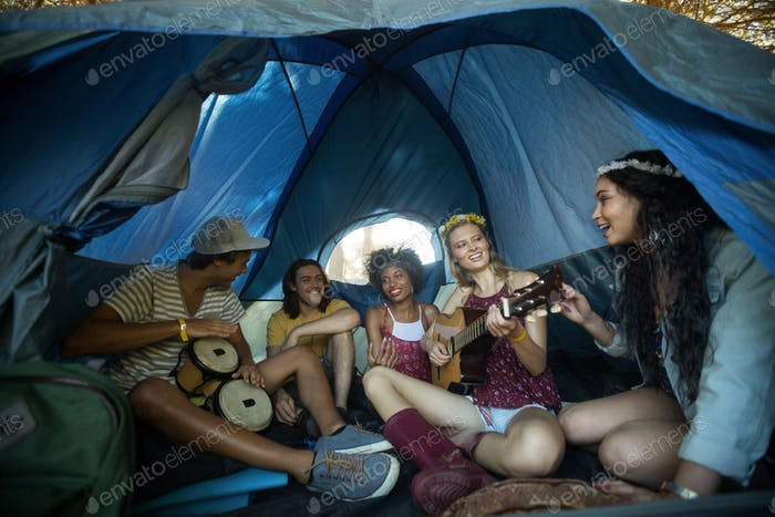 Happy young friends enjoying in tent