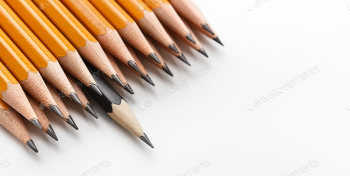 One black pencil among group of classic yellow ones