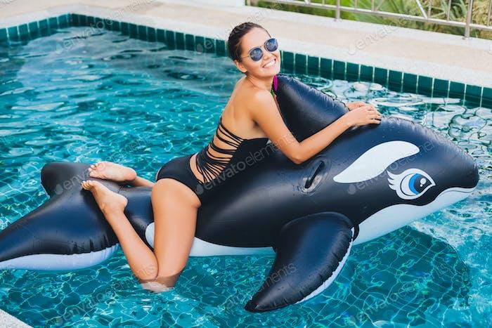 beautiful asian woman having fun in pool on tropical villa