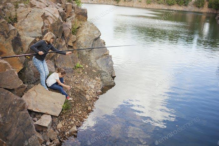 Sisters fishing in lake
