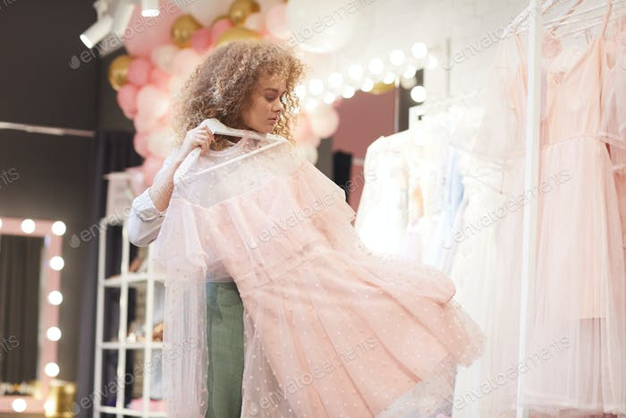 Young Woman Trying On Dresses in Boutique