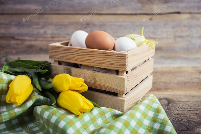 tulips and eggs on wooden background. Easter background