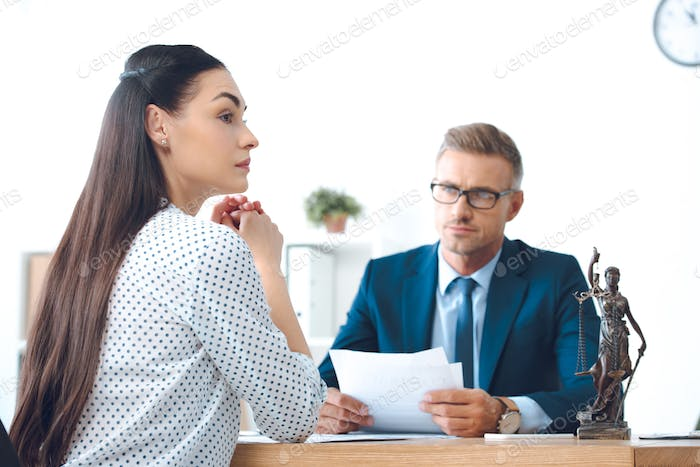 lawyer holding papers and looking at young upset woman in office