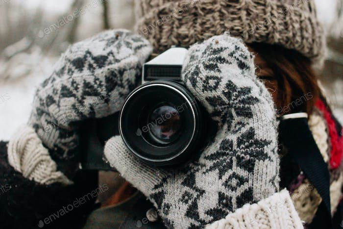happy stylish gorgeous girl with photocamera in beautiful snowy winter park