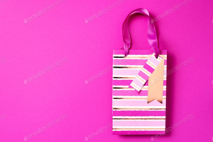 Black friday sale concept. Top view of pink paper shopping bag on trendy bright background. Copy