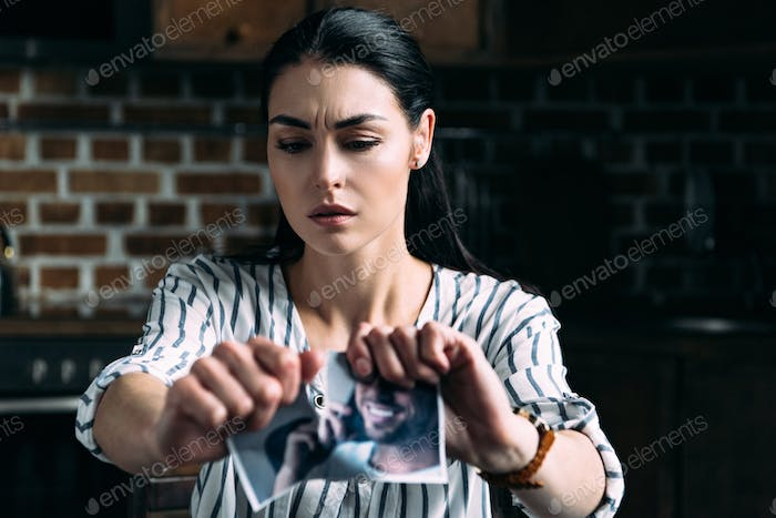 lonely young woman tearing photo of ex-boyfriend