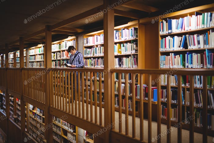 Student reading book in college library