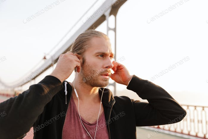 Handsome young fit sportsman listening to music