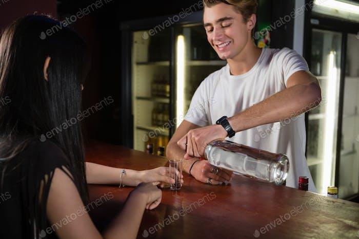 Счастливый бармен, подающий текилу клиенту