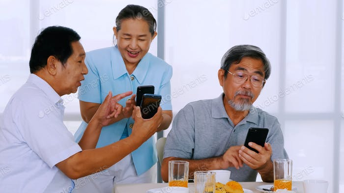 Group of senior friends using smart phone on dining table.