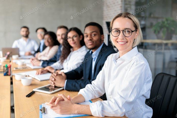 Gente de negocios multiétnica sentada teniendo una reunión corporativa en la oficina