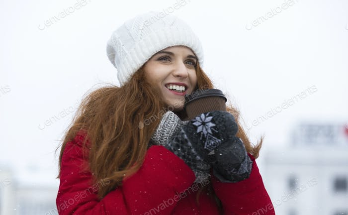 Beautiful ginger girl enjoying hot drink on winter day