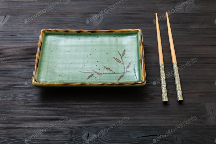 square plate and chopsticks on dark brown table