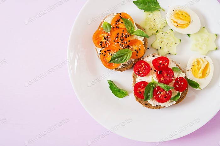 Breakfast. Sandwich with cream cheese with tomatoes and cream cheese. Top view. Flat lay